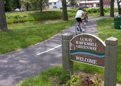 Luray Hawsksbill Greenway Welcome Sign with biker and lady on wheelchair