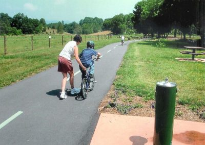 boy learning to ride a bike on the greenway